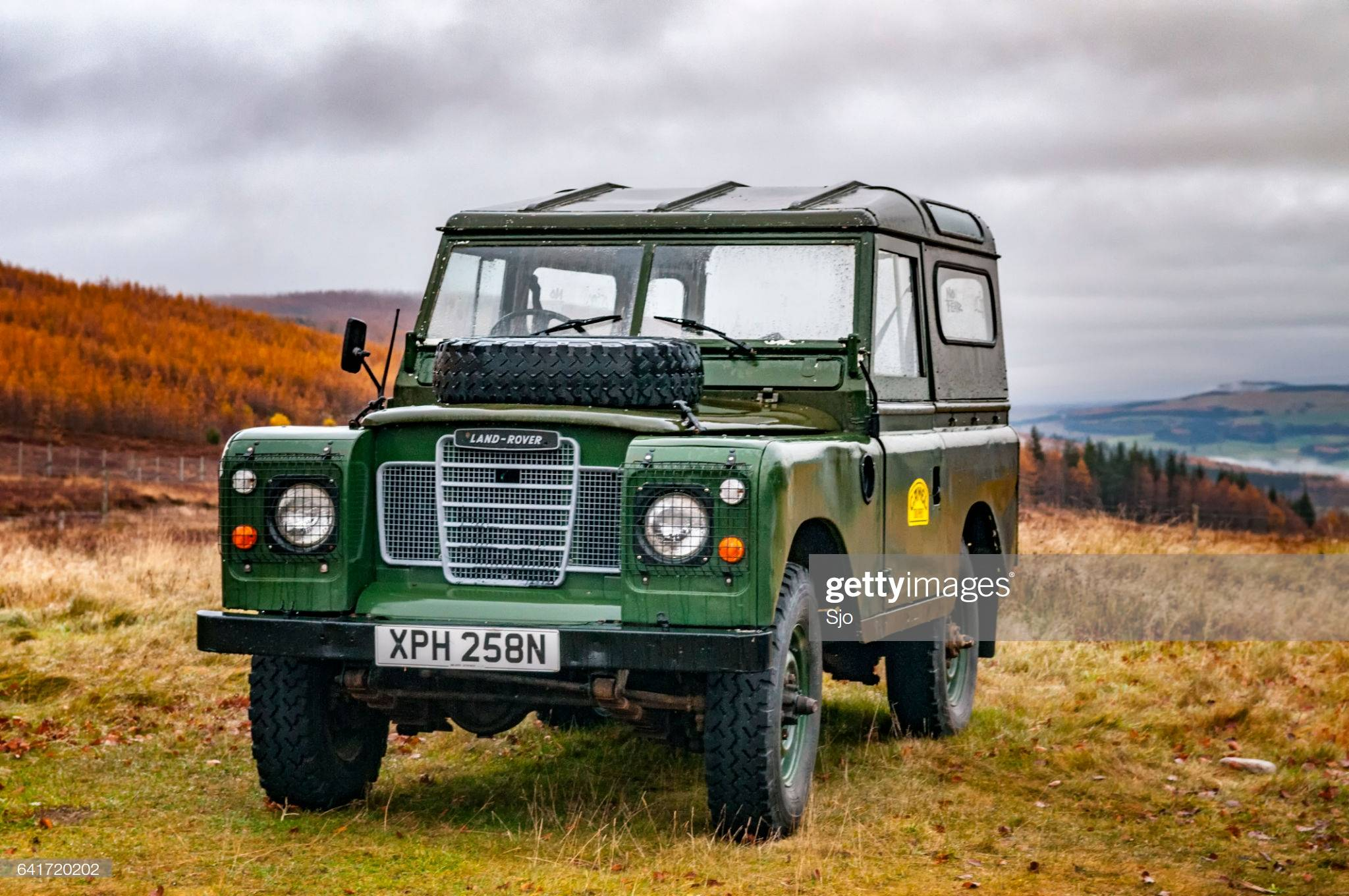 Old Land Rover Defender parked on a mountain in the Scottish Highlands near the town of Pitlochry during Autumn.